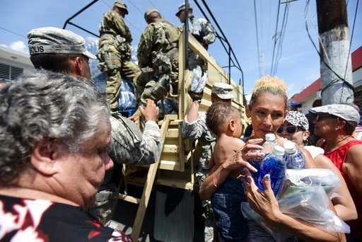 (AP Photo/Carlos Giusti). In this Sept. 24, 2017, photo, National Guard Soldiers arrive at Barrio Obrero in Santurce to distribute water and food among those affected by the passage of Hurricane Maria, in San Juan, Puerto Rico.