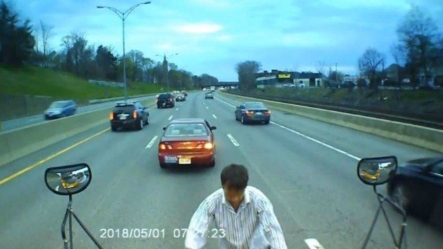 Man climbs on school bus on busy highway