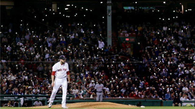 Fans turn on the flashlight on their cellphones as Boston Red Sox relief pitcher Matt Barnes walks back to the mound during the seventh inning of the team's baseball game against the Detroit Tigers at Fenway Park in Boston (AP Photo/Charles Krupa)
