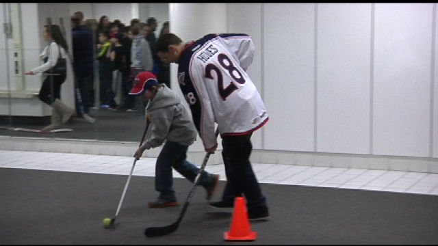 Falcons player Scott Howes shows a young fan some stick techniques