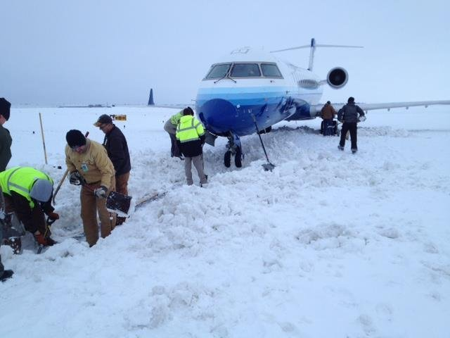 United express pilot takes a wrong way on an unplowed taxiway at Wichita Mid-Continent Airport Thursday, February 21, 2013 and gets stuck in the snow. Several people pitched in with shovels to help get the jet free. (CNN)
