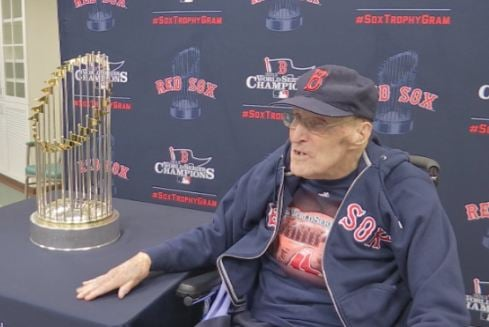 Ivan Hoyt sitting with the 2013 Red Sox World Series trophy in Londmeadow.