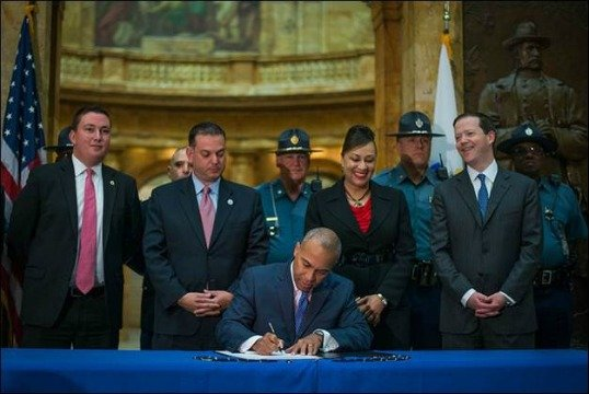 Gov. Deval Patrick signs the bill into law.