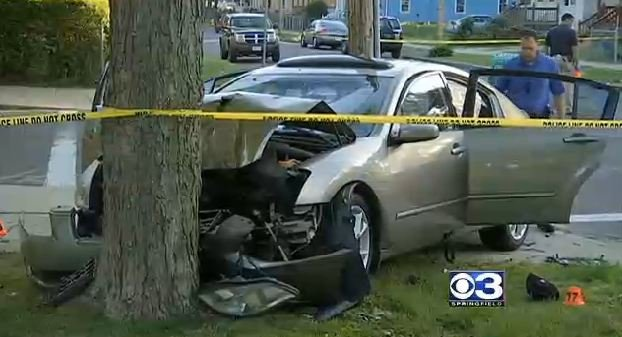 A Nissan Maxima that crashed into a tree after its front windshield was shot and its rear windshield was shattered by gunshots.