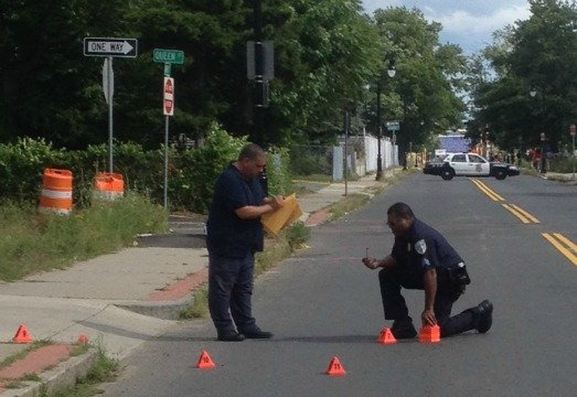 Investigators inspect a crime scene on Walnut Street after a Thursday afternoon shooting.