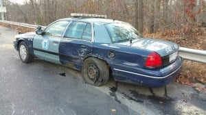 A woman with a suspended driver's license crashed into a state police cruiser while it was occupied by a trooper on Interstate 95 in Dedham on Tuesday afternoon. (MSP)
