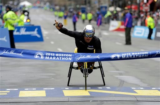Marcel Hug, of Switzerland, crosses the finish line to win the wheelchair division of the Boston Marathon, Monday, April 20, 2015, in Boston. (AP Photo/Elise Amendola)