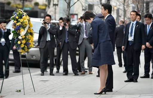 Japanese Prime Minister Shinzo Abe, center right, and his wife Akie, bow after placing a wreath at the site of one of the 2013 Boston Marathon bombings Monday, April 27, 2015, in Boston. Abe met with Secretary of State John Kerry Sunday, and planned visit