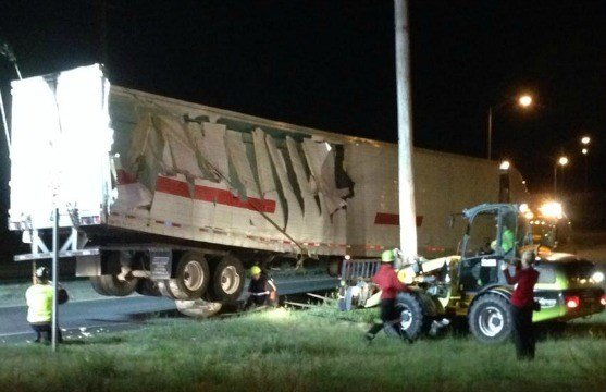 The 18-wheeler was towed away by a heavy-duty tow truck.